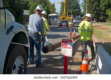 BAKERSFIELD, CA -  JUNE 17, 2019: Workmen, heavy equipment and a crane converge on a peaceful residential neighborhood to remove and replace a utility pole.