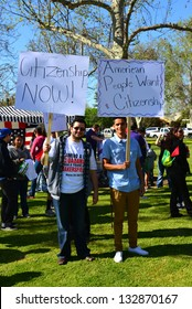 BAKERSFIELD, CA - MAR 24: Enthusiastic participants proudly wave their signs at a rally for a new immigration law on Cesar Chavez Day on March 24, 2013,  in Bakersfield, California.