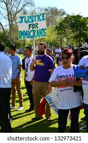BAKERSFIELD, CA - MAR 24: Enthusiastic participants wave signs and gather to get ready to march at a rally for a new immigration law on Cesar Chavez Day on March 24, 2013,  in Bakersfield, California.