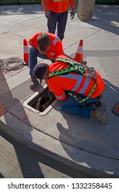 BAKERSFIELD, CA - MARCH 7, 2019: City employees work to repair traffic signal wiring in an electrical pullbox at an intersection.