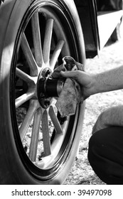 """BAKERSFIELD, CA - OCT 24: A proud owner polishes his car's brass hub and wooden wheels at the """"Rolling Thru the Ages Car Show"""" on October 24, 2009, in Bakersfield, California"""