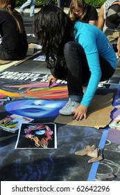 BAKERSFIELD, CA - OCT 9: Local student applies chalk to asphalt for the Via Arte Italian Street Painting Festival on October 9, 2010, at Bakersfield, California