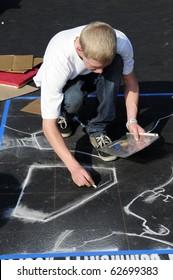 BAKERSFIELD, CA - OCT 9: Local student applies chalk to asphalt for the Via Arte Italian Street Painting Festival on October 9, 2010, in Bakersfield, California