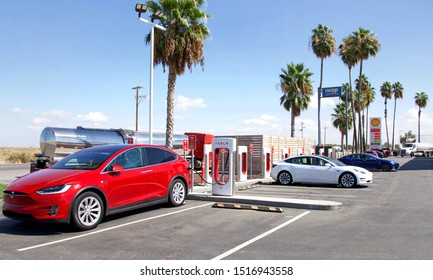 Bakersfield, CA - Sept 28, 2019: Tesla Super Charging station on Stockdale Hwy and 5 fwy. Supercharger stations allow Tesla cars to be fast-charged at the network within an hour. Gas station behind.