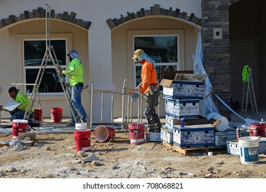 BAKERSFIELD, CA - SEPTEMBER 2, 2017: Construction workmen apply a stucco color coat to a new house in a residential development.