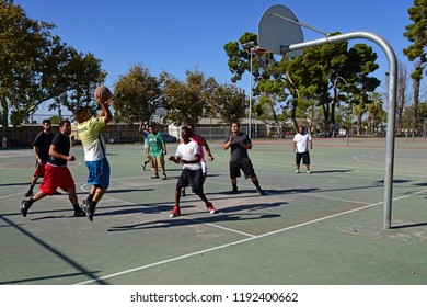 BAKERSFIELD, CA - SEPTEMBER 30, 2018: The competition is fierce as local men engage in a spirited game of pickup basketball at a nearby playground.