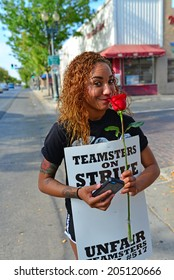 BAKERSFIELD, CA-JULY 15, 2014: After six months failed negotiations the teamsters union strikes the Golden Empire Transit District. An unidentified woman stops to smell a rose.