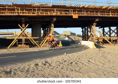 BAKERSFIELD, CA-JUN 21: Showing contrasting transportation modes, an unidentified biker must temporarily use the detour under the Westside Parkway project on June 21, 2012, in Bakersfield, California.