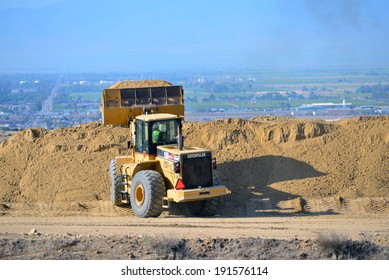 BAKERSFIELD, CA-MAY 7, 2014: A front end wheel loader quickly moves dirt along the new roadway portion as work is now about 30% complete on the widening of State Route 178.