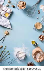 Bakery background frame. Fresh cooking ingredients - egg, flour, sugar, butter, nuts over blue background. Spring cooking theme. Top view, copy space.