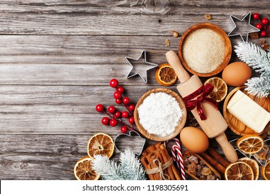 Bakery background with ingredients for cooking christmas baking decorated with fir tree. Flour, brown sugar, eggs and spices on rustic wooden kitchen table top view.