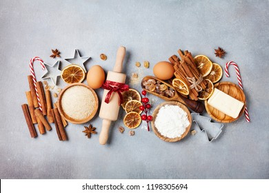 Bakery background with ingredients for cooking christmas baking. Flour, brown sugar, eggs and spices on kitchen table top view.