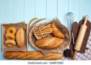Bakery Bread on blue Wooden Table. Various Bread and Sheaf of Wheat Ears .
