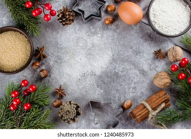 Bakery Christmas Ingredients. Flour, brown sugar, eggs, spices and holiday decoration on dark stone background. Top view with copy space.