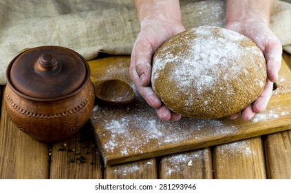 Bakery concept. Close-up view of home baked bread in male hands