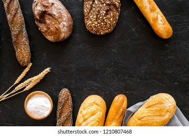 Bakery concept. Fresh white and brown bread. Loaf and baguette on tablecloth near wheat ears and flour on black background top view copy space