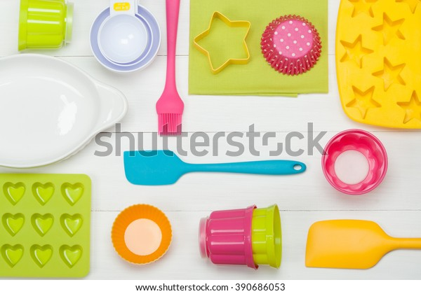 Bakery And Cooking Tools. Silicone Moulds, Cupcake Cases. Measuring Cups. Top View. White Wooden Table.