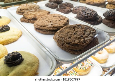 Bakery display case with trays of freshly baked cookies; sugar, oatmeal and chocolate