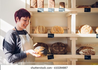 Bakery employee holding a loaf of bread