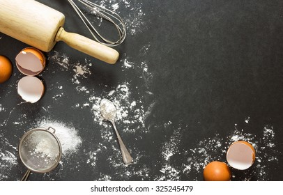 Bakery equipment and ingredient on black granite table in top view flat lay with copy space for background.Food concept to present preparing egg and flour for baking homemade cake or cookies and bread
