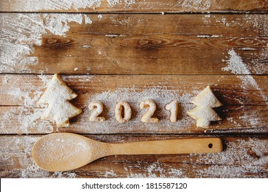 Bakery Flat lay with cookies in form of Christmas trees and numbers 2021, flour,wooden spoon on the wooden table.