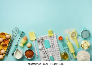 Bakery food frame, cooking concept. Different baking ingredients - butter, sugar, flour, eggs, oil, spoon, rolling pin, brush, whisk, towel over blue background. Top view, copy space. Flat lay.