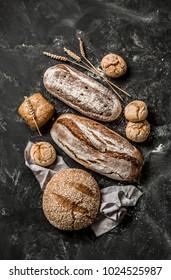 Bäckerei - goldene rustikale Krusteliebungen aus Brot und Brötchen auf schwarzem Kalkbrett-Hintergrund. Stillleben von oben erfasst (Draufsicht, flacher Lauf).