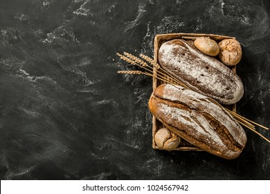 Bakery - gold rustic crusty loaves of bread and buns on black chalkboard background. Still life captured from above (top view, flat lay). Layout with free copy (text) space.