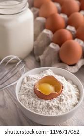 Bakery ingredients - flour, eggs, milk, yolk on a table. Sweet pastry baking concept. Closeup