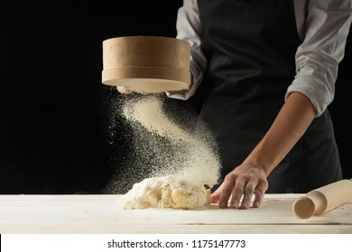 Bakery. Man preparing bread, Easter cake, Easter bread or cross-buns on wooden table in a bakery close up. Man preparing bread dough.