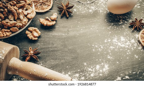 Bakery products. Cooking food ingredients: flour, eggs, nut and star anise, orange on dark table kitchen background for cake. Still life captured from above, top view, flat lay