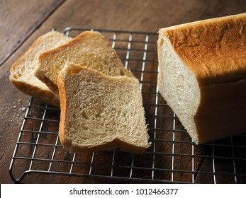 Bakery : Slices of Sandwich Bread Loaf on rack with wood background.