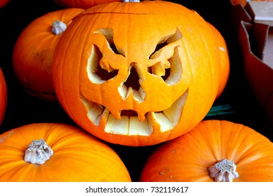 Bakewell, Derbyshire, UK. October 09, 2017. A gruesome face cut out of a pumpkin in a group of pumpkins for sale outside a grocers at Bakewell in Derbyshire.