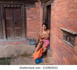 Bakhtapur, Kathmandu, Nepal - Circa September 2017 - A portrait shot of an unidentified local Nepalese woman in Bakhtapur city, Kathmandu Nepal sitting by a face brickwork wall building