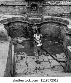 Bakhtapur, Kathmandu, Nepal - Circa September 2017 - A black and white portrait shot of an unidentified Nepalese girl collecting clean water from the tap in Bakhtapur city, Nepal