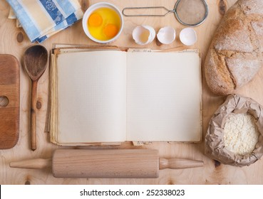 Baking background with blank cook book, eggshell, flour, rolling pin. Free space for text