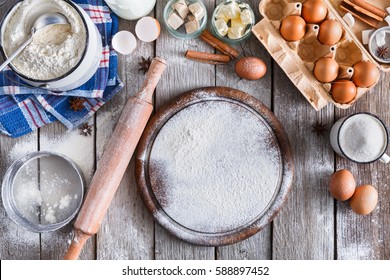 Baking background. Cooking ingredients for dough and pastry making and sprinkled with flour pizza board on rustic wood. Top view with copy space, mockup for menu, recipe or culinary classes.