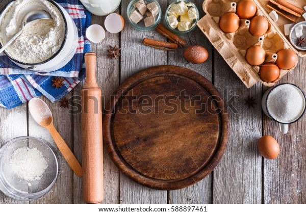Baking background. Cooking ingredients for dough and pastry making and wooden pizza board on rustic wood. Top view with copy space, mockup for menu, recipe or culinary classes.