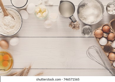 Baking background. Cooking ingredients for doughand utensils, eggs, flour, sugar and butter on white rustic wood, recipe or culinary classes, copy space, top view