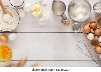 Baking background with copy space. Cooking ingredients for dough and pastry, eggs, flour and butter on white rustic wood. Top view, mockup for menu, recipe or culinary classes.