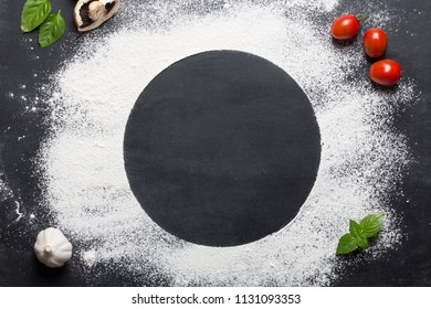Baking background with copy space on black surface for your text. Top view. Flour is a traditional ingredient for breadmaking and other baking. Often used in Italian cuisine