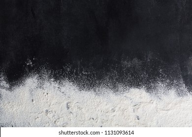 Baking background with copy space on black surface for your text. Top view. Flour is a traditional ingredient for breadmaking and other baking. Often used in Italian, Arabic and Chinese cuisines for b