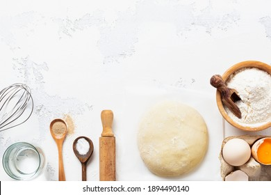 Baking background with dough and ingredients for the preparation of pasta or pancakes, eggs, flour, water and salt on white rustic old table. Top view.