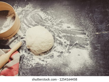 Baking background with dough, rolling pin and flour on dark table. Toned photo