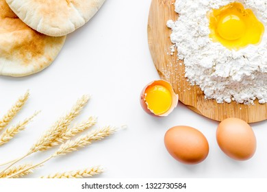 Baking background with eggs, flour and bread on white desk. Top view.