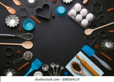 Baking background with eggs and kitchen tools: rolling pin, wooden spoons, whisk, sieve, bakeware and shape cookie cutter on dark wooden background. Horizontal orientation with copyspace, top view.