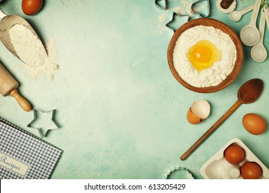 Baking background with flour, eggs and kitchen tools on blue rustic table. Top view. Flat lay style.