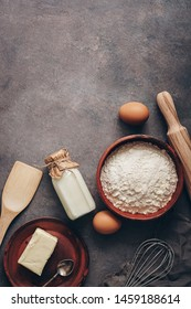Baking background, flour, rolling pin, bottle of milk, butter and eggs on a dark rustic background. Top view, flat lay, copy space