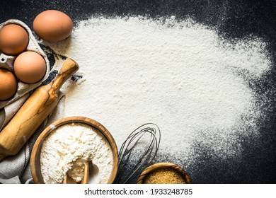 Baking background. Flour, sugar, eggs, spices and utensil on black table. Top view with copy space.