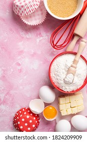 Baking background. Food ingredients for baking flour, eggs, sugar on pink background flat lay. Baking or cooking cakes or muffins. Top view